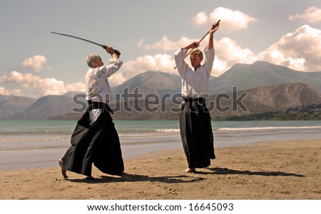 two adults are training in aikido on a beach in japon - stock photo