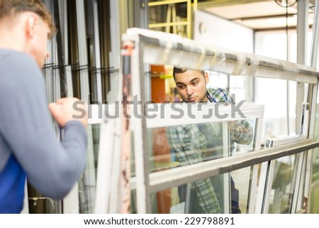Two adults working in uniform examining a window at workshop - stock photo