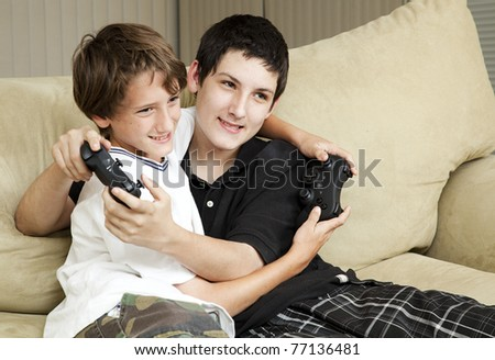 Two affectionate brothers playing video games together.