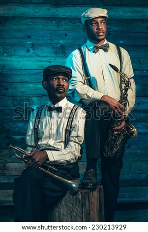 Two african american jazz musicians with trumpet and saxophone standing in front of old wooden wall. - stock photo