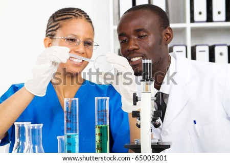two african american lab technicians doing experiment in lab