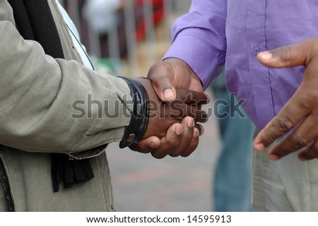 Two African American men shaking their black hands as a sign of big friendship and to say goodbye - stock photo