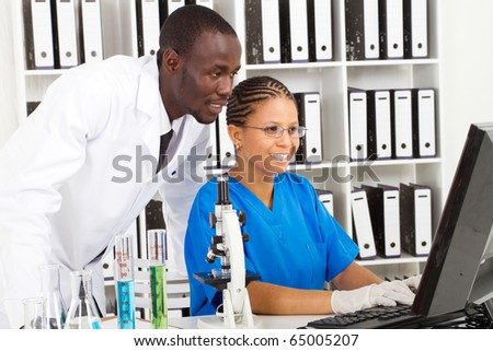 two african american scientists working in lab together