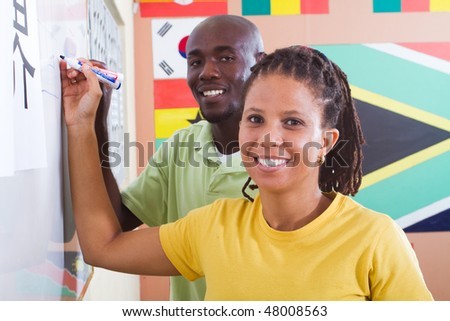 two african american students learning chinese in classroom - stock photo