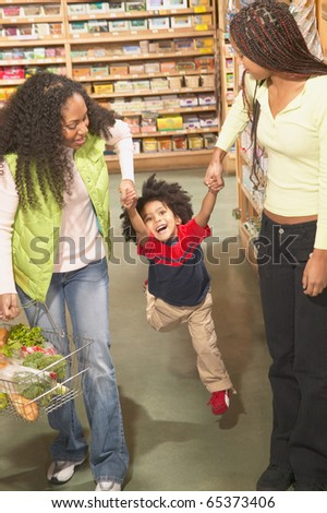 Two African American women with young boy in health food store