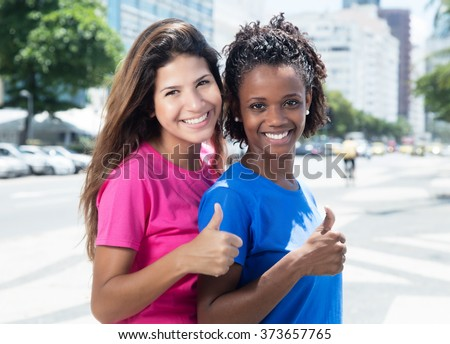 Two african and caucasian women showing thumb in the city - stock photo