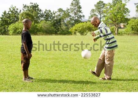 two african boys paly football in the park - stock photo