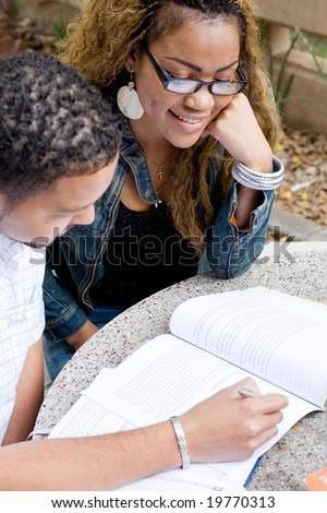 Two african college students friends study a book together outdoors - stock photo