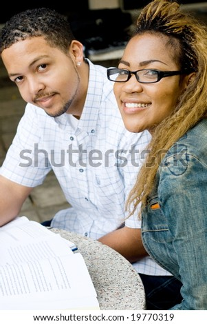 Two african college students friends study together outdoors - stock photo