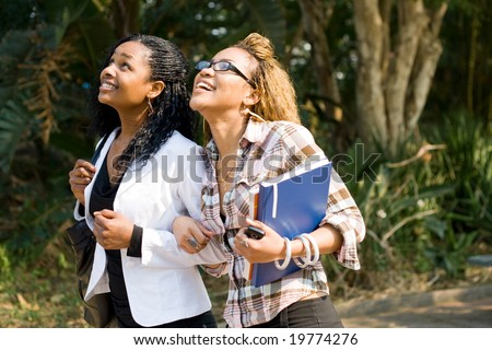 two african female college students walking to school classroom - stock photo