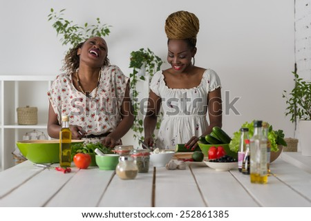 Two african women cooking in kitchen making healthy food salad with vegetables - stock photo