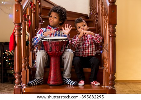 Two afro boys play music. Kids playing music on stairs. Creative duet of young musicians. Starting a music tour. - stock photo