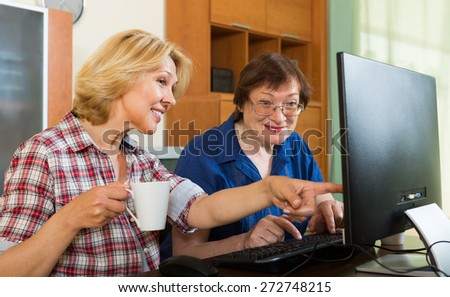Two aged female colleagues looking at PC screen and smiling