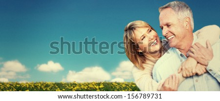 Two aged smiling people over sky background - stock photo