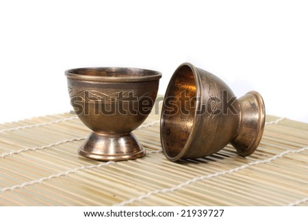 Two aged steel cups on bamboo norri