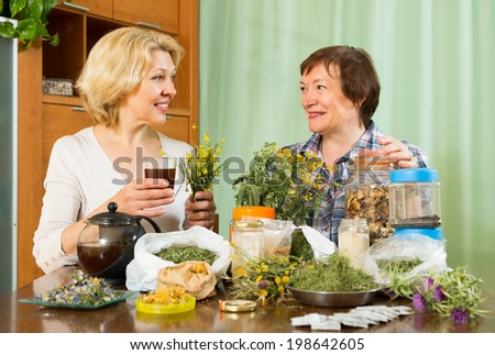 Two aged women with medicinal herbs brewing herbal tea at the table