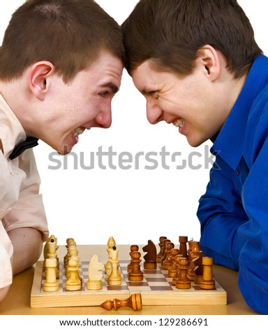 Two aggressive chess opponents fights with his forehead under chess board - stock photo