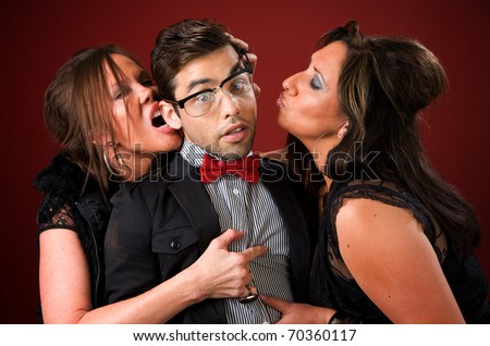 Two aggressive cougar women corner a shy young man - stock photo