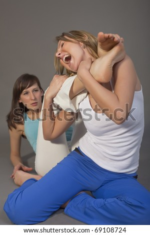 two aggressive women fighting over grey background - stock photo