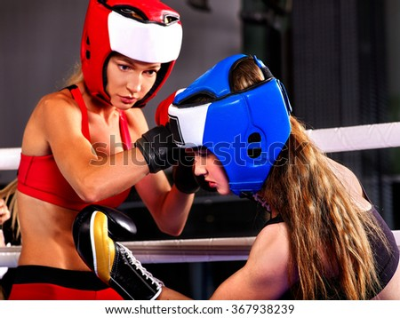 Two agressive women boxer wearing helmet boxing at ring . - stock photo