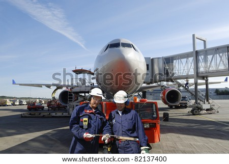 two air mechanics, engineers, with large airliner in background, airport ground activities - stock photo