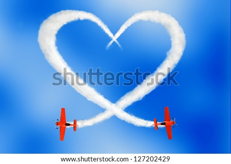 two air-planes drawing a cloudy love is in the air concept in the sky with smoke - stock photo