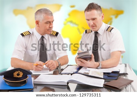 Two airline pilots preparing to flight, checking calculator, papers, flight plan, log book. Pilots are sitting in AIS ARO Air Traffic Services Reporting Office - stock photo