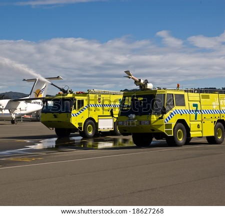 Two airport fire trucks shooting water - stock photo
