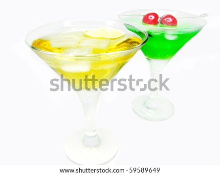 two alcohol green and yellow liqueur cocktail with ice cherry and lemon