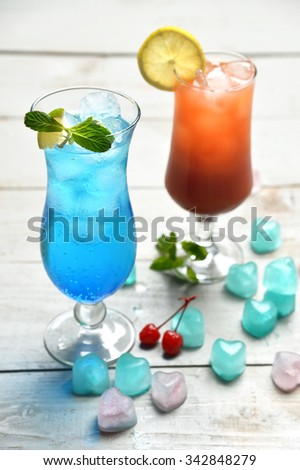 Two alcohol margarita martini cocktail and blue lagoon with lemon lime and cherry in cocktails glasses on rustic wood background - stock photo