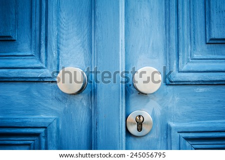 Two aluminium elegant door handle on a vintage blue painted door - stock photo