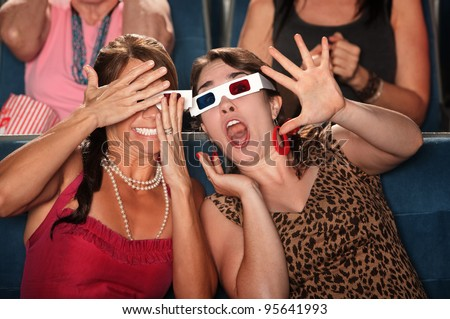 Two amazed women with 3d glasses react to a movie - stock photo