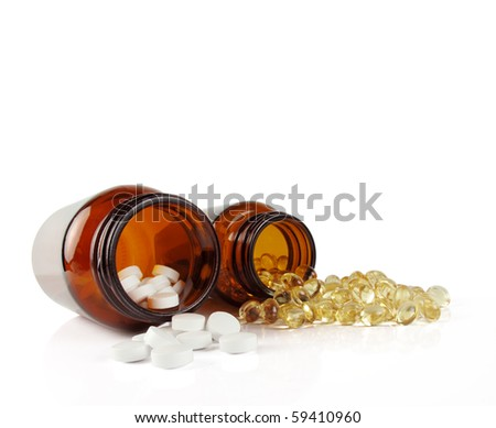 Two amber vitamin bottles with contents spilled in front - stock photo