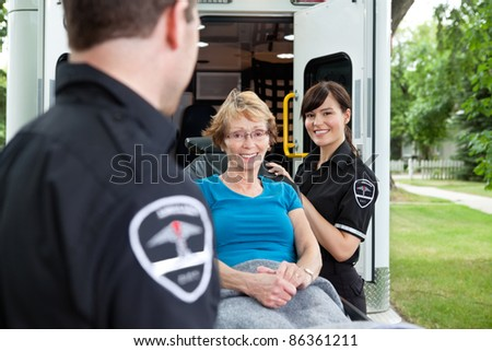 Two ambulance workers pushing a happy femaile patient - stock photo