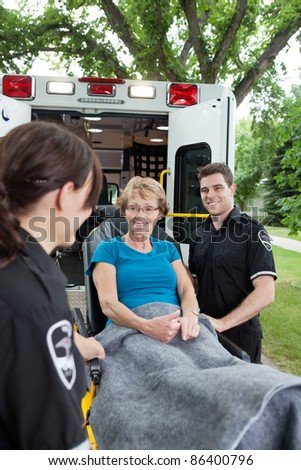 Two ambulance workers pushing a happy senior woman on a stretcher - stock photo