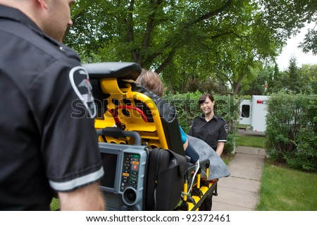 Two ambulance workers pushing elderly patient to vehicle - stock photo