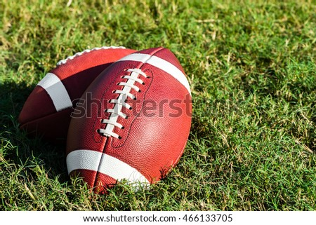 Two American college high school junior striped footballs on green grass football field