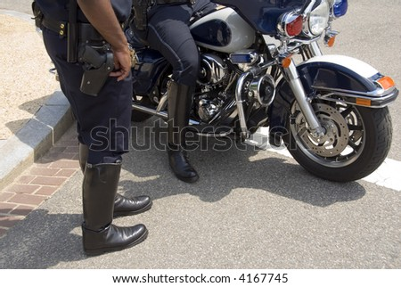 Two American motorcycle policemen, one seated on a patrol bike, talking in the summer sunshine. - stock photo