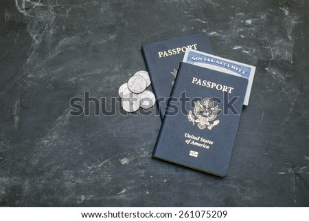 Two American passports on black background. American citizenship. Social security card in a document. Traveling around the world. Coins on a side - stock photo