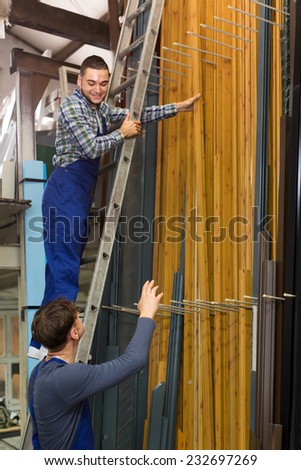 Two american workers choosing PVC window profile at stand - stock photo