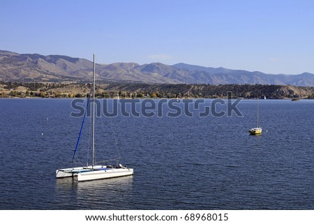 Two anchored sailboats in a lake setting - stock photo