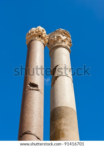 Two ancient roman pillars against a blue sky