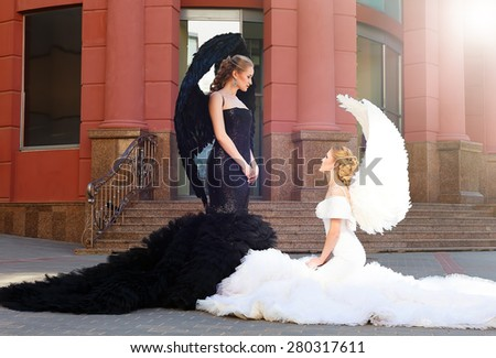 two angels. white and black angels.good and evil. black angel standing over white angel - stock photo