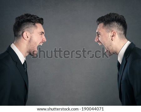 Two angry businessman facing each others. Studio portrait against grunge background. - stock photo