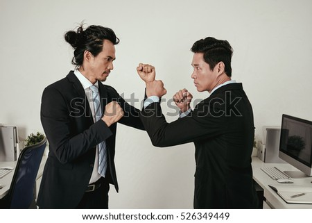 Two angry businessmen almost fighting in office