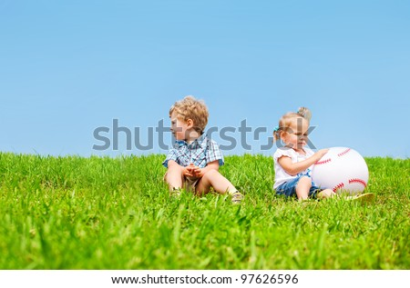 Two angry kids sit on grass - stock photo