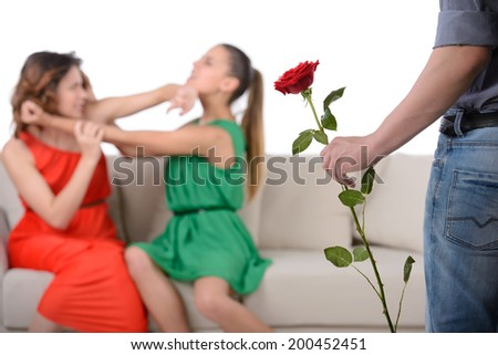 Two angry woman fighting for a man, isolated over white background - stock photo