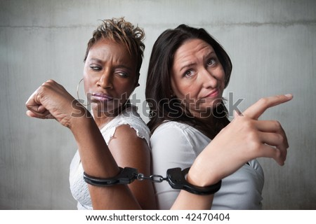 Two angry women connected by a pair of handcuffs - stock photo