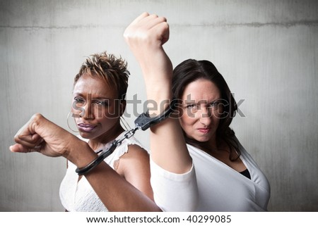 Two angry women joined by a pair of handcuffs - stock photo