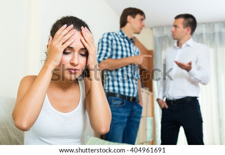 Two angry young guys and offended girl apart after conflict indoors